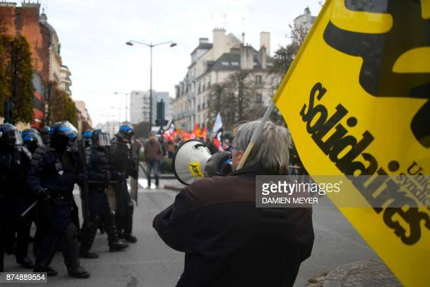 A demonstrator uses a megaphone in front of police forces during a demonstration as part of a nationwide protest day against the government's...