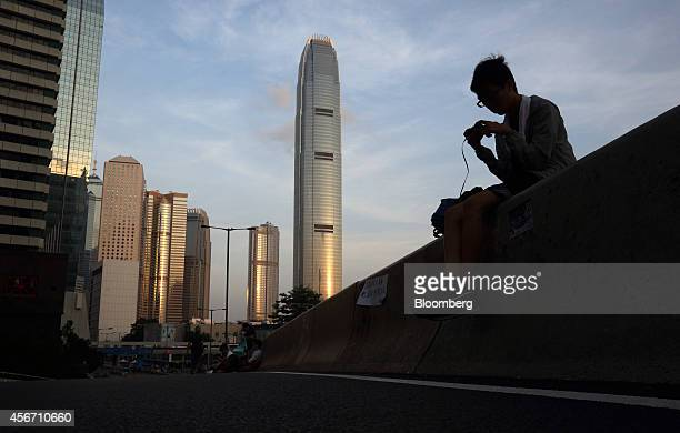 A demonstrator uses a mobile device during a protest outside the Central Government Offices in Hong Kong China on Monday Oct 6 2014 Prodemocracy...