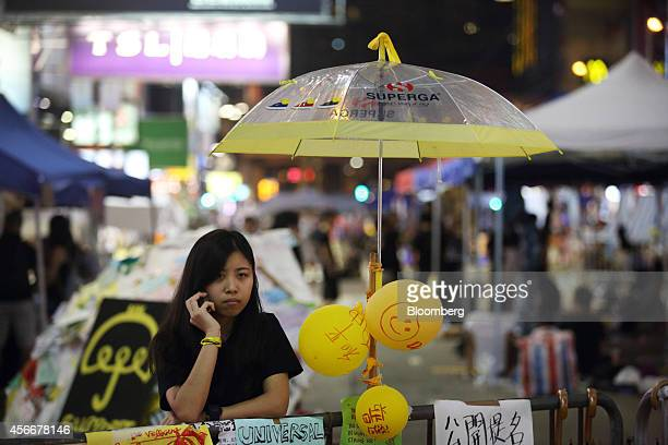 A demonstrator uses a mobile phone as she stands behind a barricade in the Causeway Bay area of Hong Kong China on Sunday Oct 5 2014 Hong Kong...