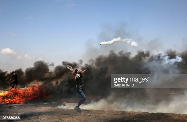 TOPSHOT A demonstrator uses a racket to return a tear gas canister fired by Israeli troops during clashes along the border with the Gaza strip east...