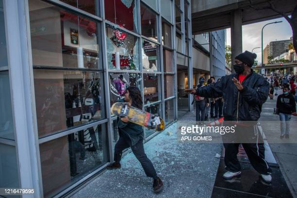TOPSHOT A demonstrator uses a shakeboard to vandalize a restaurant in Downtown Los Angeles on May 30 2020 during a protest against the death of...