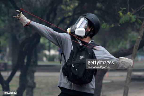 A demonstrator uses a slingshot against riot police during protests against president Piñera at Plaza Italia on December 2 2019 in Santiago Chile To...