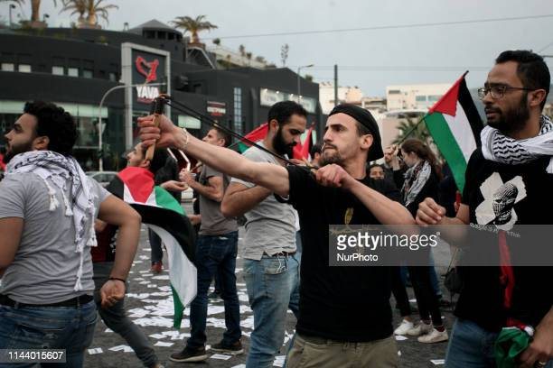 A demonstrator uses a slingshot to throw stones during a protest rally by Palestinians outside the embassy of Israel in Athens Greece on May 15 2019...