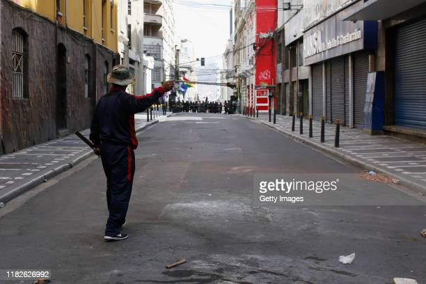 A demonstrator uses a throwing weapon against military police during a protest on November 15 2019 in La Paz Bolivia Morales flew to Mexico alleging...
