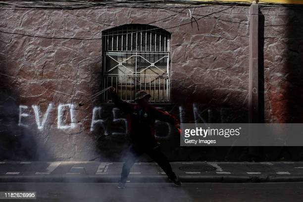 A demonstrator uses a throwing weapon against military police in front of a wall with the graffiti that reads 'Evo murderer' during a protest on...
