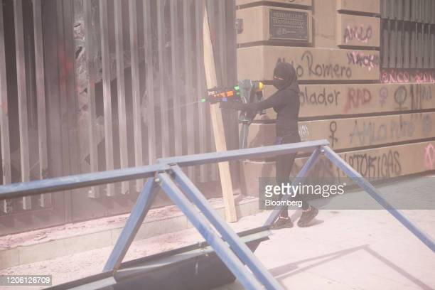 A demonstrator uses a water gun to spray gasoline into a building during a rally on International Women's Day in Mexico City Mexico on Friday March 8...