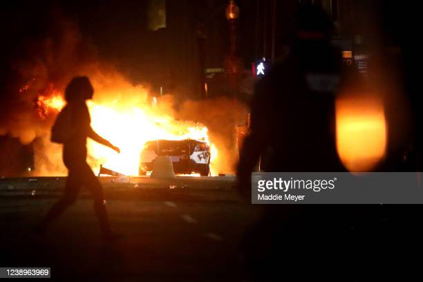 Demonstrator walks in front of a Police car that has been lit on fire in response to the recent death of George Floyd on May 31, 2020 in Boston,...