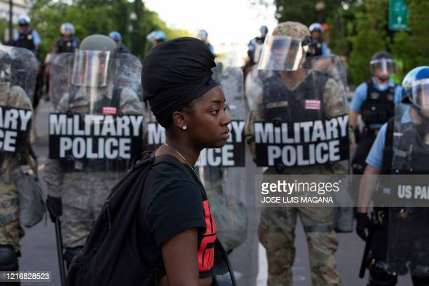 A demonstrator walks in front of a row of military police members wearing riot gear as they push back demonstrators outside of the White House June 1...