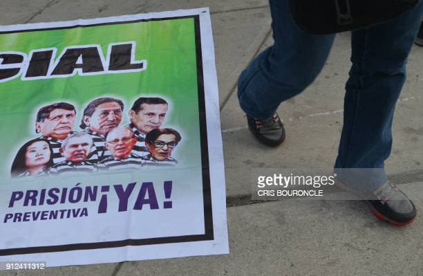 A demonstrator walks past a banner calling for preventive detention of Peruvian former presidents Alan Garcia Alejandro Toledo and Ollanta Humala...