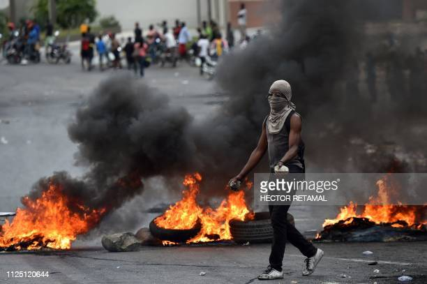 TOPSHOT A demonstrator walks past next to barricades during clashes with Haitian police in PortauPrince on February 15 on the ninth day of protests...