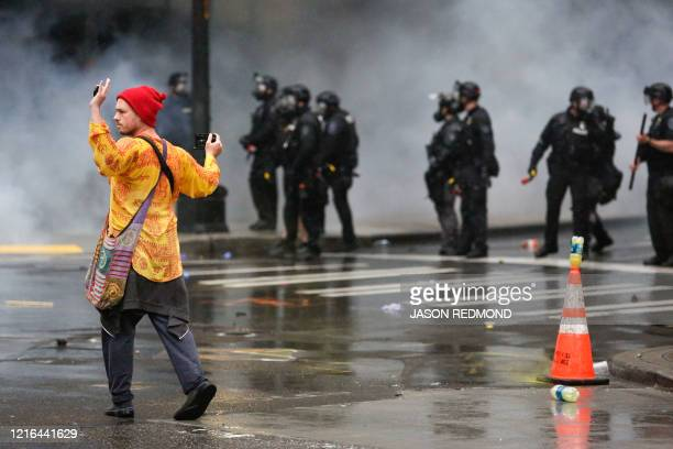 A demonstrator walks past police officers after protests against the death of George Floyd a black man who died May 25 in the custody of Minneapolis...