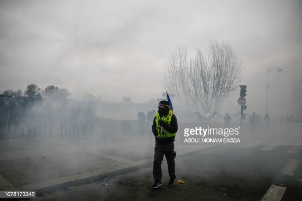 A demonstrator walks through a cloud of teargas in Paris on January 5 during an antigovernment demonstration called by the yellow vest 'Gilets...
