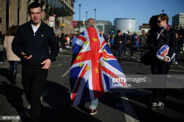 A demonstrator walks with a Union flag draped over his back following an anti Brexit proEuropean Union march in London on March 25 ahead of the...