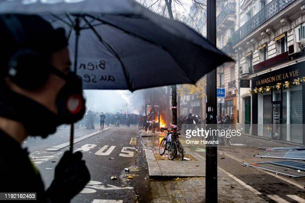 A demonstrator walks with an umbrella in front of a burning bus stop during the first day of an indefinite general strike on December 05 2019 in...