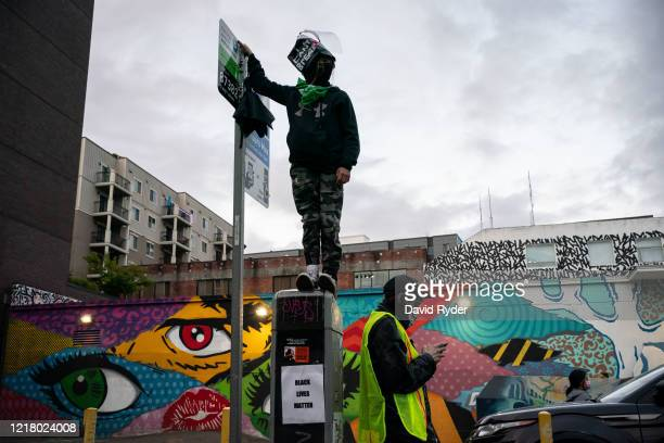 Demonstrator watches as others face off with police near the Seattle Police Departments East Precinct on June 6, 2020 in Seattle, Washington. This is...