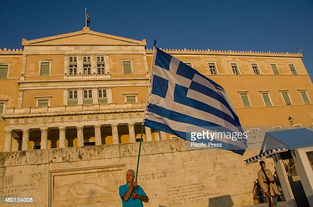 A demonstrator waves a big Greek flag in front of the Greek parliament Greek citizens gather in Syntagma square under the slogan 'We stay in Europe'...