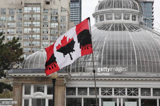 Demonstrator waves a Canadian flag dripping with oil as hundreds took part in a massive march against climate change during the North American Day of...