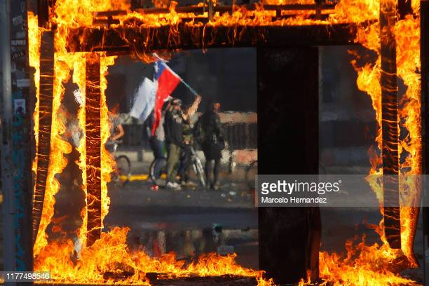 A demonstrator waves a Chilean flag during a protest against President Sebastian Piñera on October 21 2019 in Santiago Chile President Sebastian...