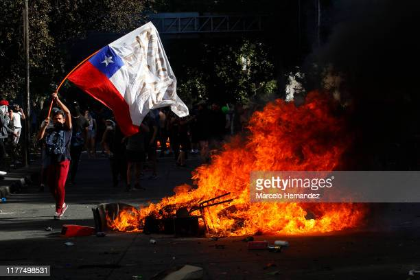 Demonstrator waves a Chilean flag next to a fire as clashing with riot police during a protest against President Sebastian Piñera on October 21, 2019...