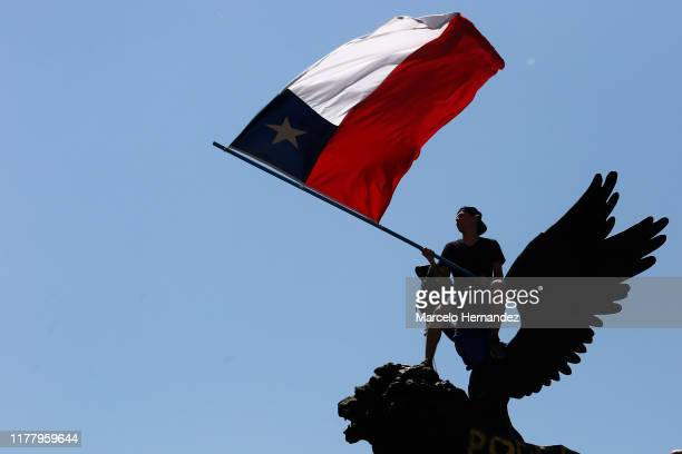 A demonstrator waves a Chilean flag on top of a monument during the seventh day of protests against President Sebastian Piñera on October 24 2019 in...