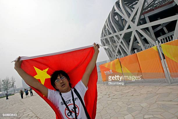 A demonstrator waves a Chinese flag and wears a shirt with an antiCNN logo outside the Olympic National Stadium in Beijing China on Friday April 18...