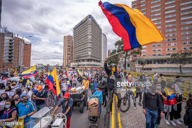 Demonstrator waves a Colombian flag while others walk by as part of a march during national strike on May 5, 2021 in Bogota, Colombia. Despite that...