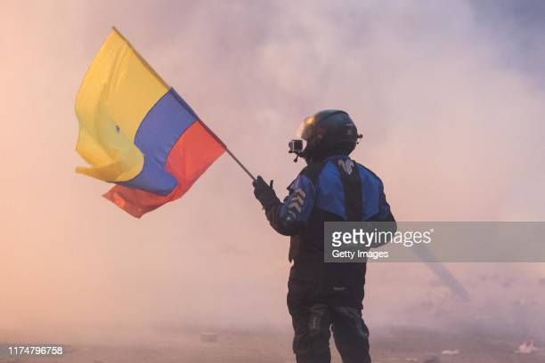 A demonstrator waves a Ecuadorian flag during a clash with the police as part of the protests against the end of subsidies to gasoline and diesel...
