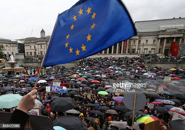 A demonstrator waves a European flag as people shelter under umbrellas at an antiBrexit protest in Trafalgar Square in central London on June 28 2016...