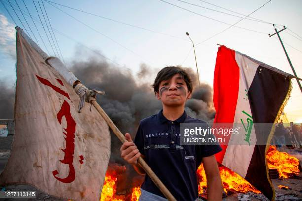 Demonstrator waves a flag bearing the name of Imam Hussein, the grandson of Prophet Mohammed, during a protest in the southern city of Basra on July...