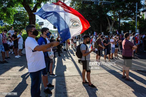 Demonstrator waves a flag of Paraguay during a protest against President Mario Abdo Benitez amid coronavirus pandemic near the presidential house on...