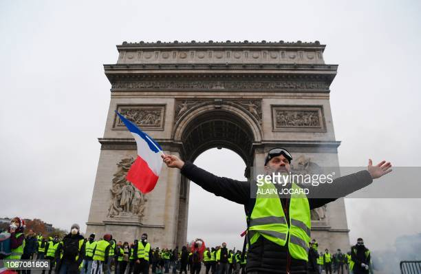 Demonstrator waves a French national flag during a protest of Yellow vests against rising oil prices and living costs in front of the Arc of Triomphe...
