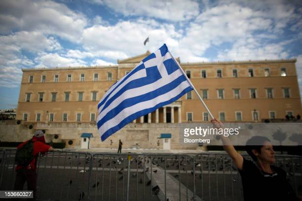 A demonstrator waves a Greek national flag ahead of a protest against tomorrow's visit by Angela Merkel Germany's chancellor opposite the Greek...