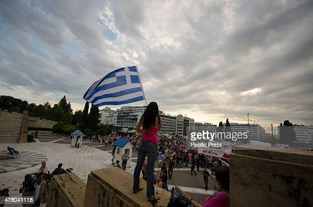 A demonstrator waves a huge Greek flag Greeks gathered in Syntagma square demanding dignity and to stop the austerity measures imposed in Greece by...