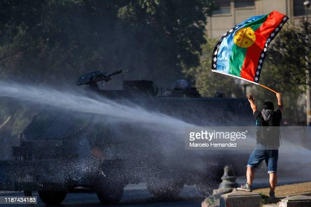 Demonstrator waves a Mapuche flag as he observes a water cannon firing during the protest against government of President Sebastian Piñera on...