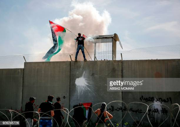 TOPSHOT A demonstrator waves a Palestinian flag after climbing the controversial separation wall near the occupied West Bank village of Bilin near...