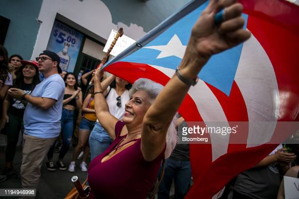 A demonstrator waves a Puerto Rican flag during a protest against the government in San Juan Puerto Rico on Monday Jan 20 2020 People in a southern...
