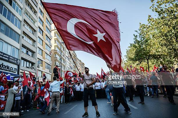 TOPSHOT A demonstrator waves a Turkish flag near Istanbul's Taksim Square on July 24 2016 during the first crossparty rally to condemn the coup...