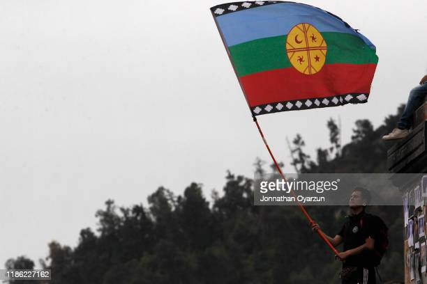 A demonstrator waves a wenufoye flag a symbol of Mapuche communities during protests against president Piñera at Plaza Italia on December 2 2019 in...