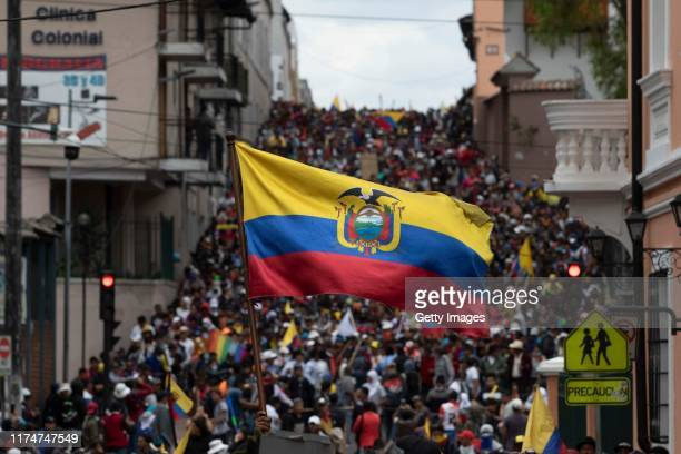Demonstrator waves an Ecuadorian flag near the Presidential Palace of Carondelet during protests against the end of subsidies to gasoline and diesel...