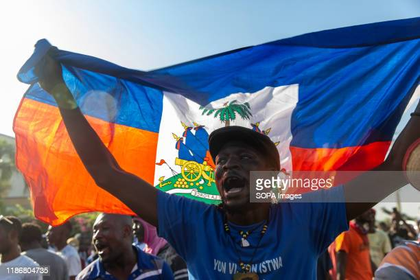 A demonstrator waves the Haitian flag while chanting antiAmerican slogans during the protest outside the US Embassy For over a year tensions has been...