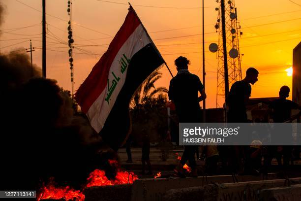 Demonstrator waves the national flag during a protest in the southern city of Basra on July 14 as they block the road to denounce the lack of...