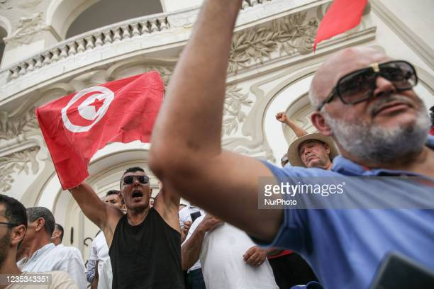 Demonstrator waves the Tunisian flag as he shouts slogans, during a demonstration held in the capital Tunis, Tunisia, on September 18 to protest what...