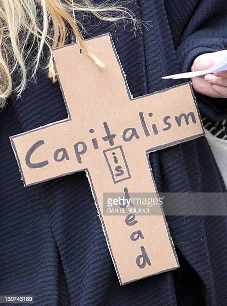 A demonstrator wear a cross reading capitalism is dead while taking part in a protest march as part of the Occupy Frankfurt movement in Frankfurt am...