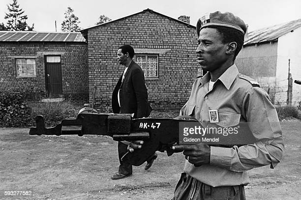 A demonstrator wearing a button of African National Congress President Oliver Tambo marches with an AK47 replica during the funeral procession for...