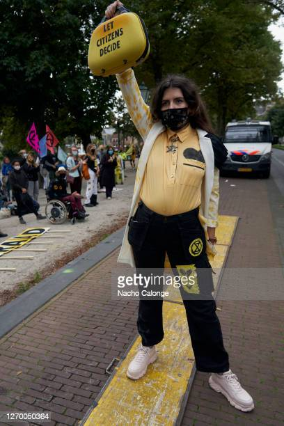 A demonstrator wearing a costume holds a sign to ask the government to take into account the opinion of citizens during the demonstration in The...