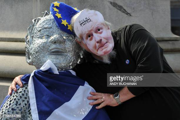 A demonstrator wearing a defaced mask depicting Britain's Prime Minister Boris Johnson joins a protest against the British government's move to...
