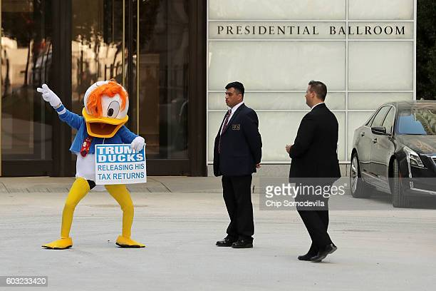 A demonstrator wearing a Donald Duck costume dances in front of the Trump International Hotel during the hotel's first day of business September 12...