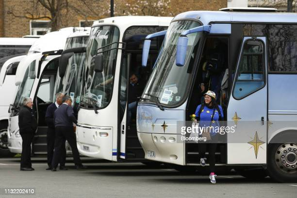 A demonstrator wearing a European Union flag shirt exits a coach ahead of the antiBrexit People's Vote rally in London UK on Saturday March 23 2019...