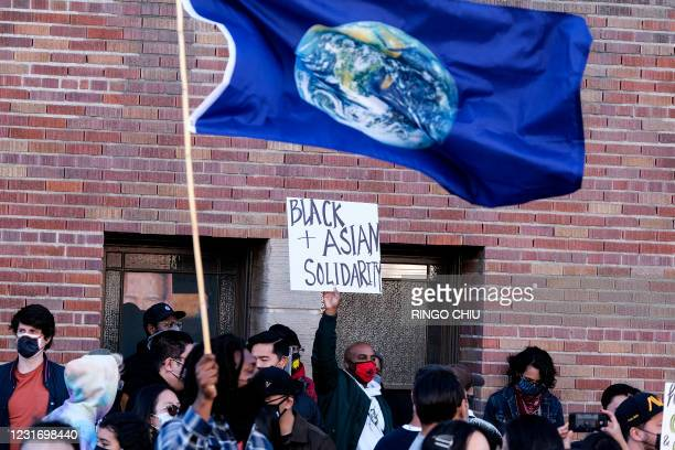 """Demonstrator wearing a face mask and holding a sign calling for """"Black Asian Solidarity"""" takes part in a rally """"Love Our Communities: Build..."""