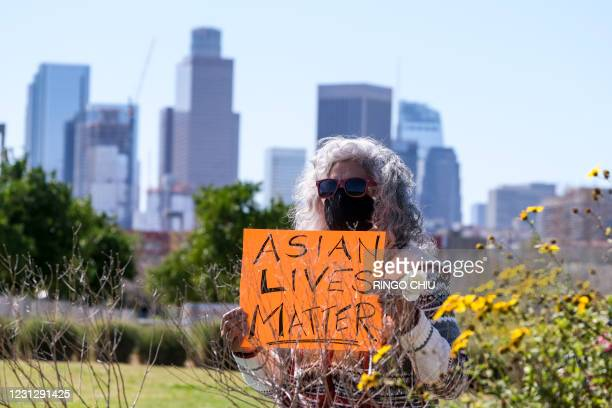 Demonstrator wearing a face mask and holding a sign takes part in a rally to raise awareness of anti-Asian violence, near Chinatown in Los Angeles,...